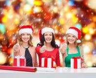 Усмехаясь женщины в шляпах хелпера santa с подарочными коробками Стоковое фото RF