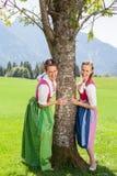 2 усмехаясь женщины в dirndl держат дальше к дереву Стоковое Изображение