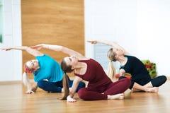 3 усмехаясь женщины делают протягивать тренировку в спортклубе Спортзал фитнеса Стоковые Изображения RF