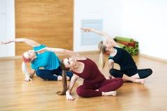 3 усмехаясь женщины делают протягивать тренировку в спортклубе Спортзал фитнеса Стоковое Изображение