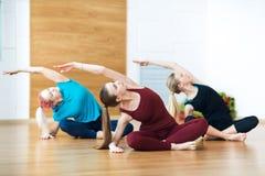 3 усмехаясь женщины делают протягивать тренировку в спортклубе Спортзал фитнеса Стоковая Фотография