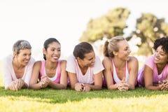 Усмехаясь женщины лежа в ряд и нося пинк для рака молочной железы Стоковое Фото
