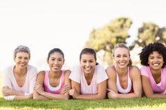 Усмехаясь женщины лежа в ряд и нося пинк для рака молочной железы Стоковая Фотография