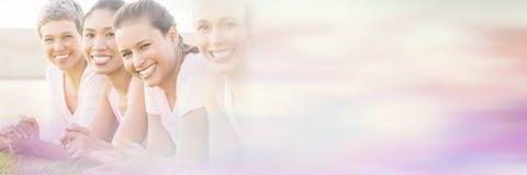 Усмехаясь женщины лежа в строке и нося пинке для рака молочной железы Стоковые Фото