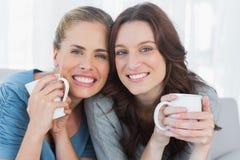 Усмехаясь женщины держа их чашку кофе Стоковая Фотография