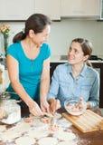 Усмехаясь женщины делая пироги или вареники мяса Стоковые Фото