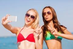 2 усмехаясь женщины делая selfie на пляже Стоковые Изображения