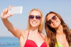 2 усмехаясь женщины делая selfie на пляже Стоковое Изображение RF