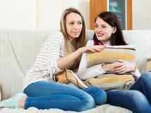 Усмехаясь женщины злословя на софе Стоковое фото RF