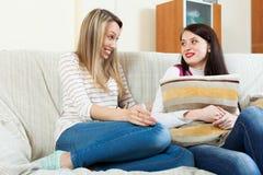 Усмехаясь женщины злословя на софе Стоковая Фотография RF