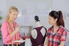 2 усмехаясь женщины используя швейную машину пока держащ яркую ткань стоковая фотография rf
