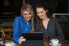 Усмехаясь женщины используя цифровую таблетку в кофейне Стоковое Изображение