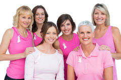 Усмехаясь женщины представляя и нося пинк для рака молочной железы Стоковые Изображения