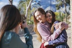 2 усмехаясь женщины представляя к женскому фотографу Стоковая Фотография RF