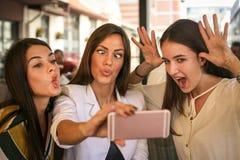 Усмехаясь женщины принимая selfie совместно outdoors Девушки делая funn Стоковые Фотографии RF