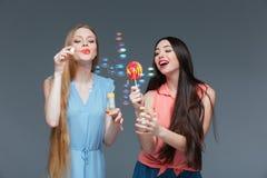 2 усмехаясь женщины при красочный леденец на палочке стоя и дуя клокочут стоковое фото