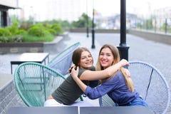 Усмехаясь женщины сидя на кафе снаружи Стоковое фото RF