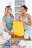 Усмехаясь женщины сидя на поле с хозяйственной сумкой Стоковая Фотография