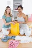 Усмехаясь женщины сидя на поле с хозяйственной сумкой Стоковое Изображение RF