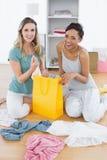 2 усмехаясь женщины сидя на поле с хозяйственной сумкой Стоковое Фото