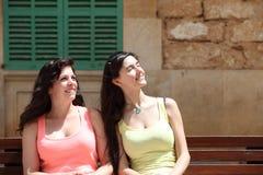 Усмехаясь женщины сидя на стенде смотря вверх Стоковая Фотография