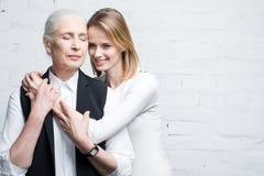 Усмехаясь женщины смотря в сторону и обнимать один другого Стоковые Фото
