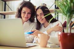 2 усмехаясь женщины смотря компьтер-книжку совместно Стоковые Изображения RF