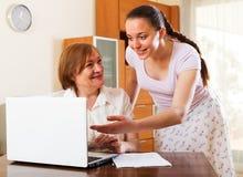 Усмехаясь женщины смотря финансовые документы в компьтер-книжке Стоковое Изображение RF