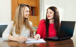 Усмехаясь женщины смотря финансовые документы Стоковое Фото