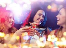 Усмехаясь женщины с коктеилями на ночном клубе Стоковая Фотография