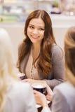Усмехаясь женщины с кофейными чашками в моле или кафе Стоковая Фотография RF
