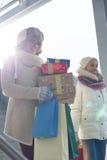 Усмехаясь женщины с подарками и хозяйственными сумками окном во время зимы Стоковая Фотография