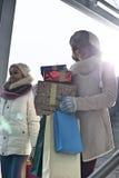 Усмехаясь женщины с подарками и хозяйственными сумками окном во время зимы Стоковое Фото