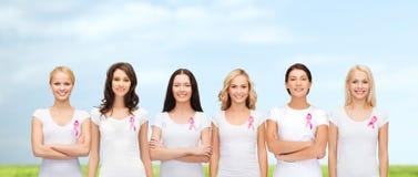 Усмехаясь женщины с розовыми лентами осведомленности рака Стоковая Фотография