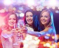 Усмехаясь женщины с стеклами шампанского на ночном клубе стоковое фото rf