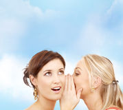 2 усмехаясь женщины шепча сплетне Стоковые Изображения
