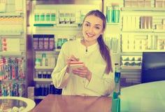 Усмехаясь жизнерадостный молодой женский представлять аптекаря Стоковая Фотография