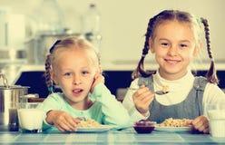 2 усмехаясь жизнерадостных девушки есть здоровую овсяную кашу Стоковые Изображения RF