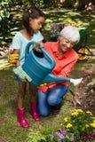 Усмехаясь заводы бабушки и девушки моча Стоковое Фото