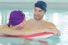 Усмехаясь заплывание человека и женщины в бассейне Стоковая Фотография