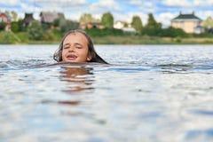 Усмехаясь заплывы девочка-подростка в русском пригородном озере летом стоковое изображение rf