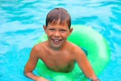 Усмехаясь заплывы мальчика в бассейне стоковые изображения rf
