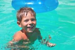 Усмехаясь заплывы мальчика в бассейне стоковое изображение rf