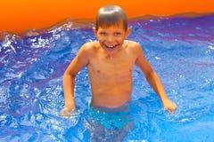 Усмехаясь заплывы мальчика в бассейне стоковые фотографии rf