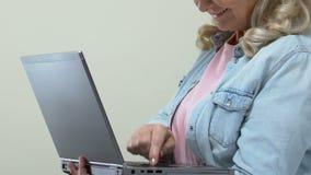 Усмехаясь зрелая женская печатая электронная почта на клавиатуре ноутбука, современной технологии, устройстве видеоматериал