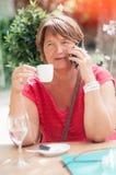 Усмехаясь зрелая женщина говоря на smartphone и выпивая кофе i Стоковое Изображение