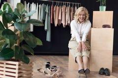 усмехаясь зрелая женщина пробуя на ботинках Стоковая Фотография