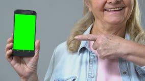 Усмехаясь зрелая женщина указывая на смартфон в руке, зеленом экране, применении видеоматериал
