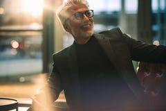 Усмехаясь зрелый бизнесмен сидя в лобби офиса Стоковая Фотография RF