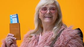 Усмехаясь зрелый женский рюкзак держа билеты и паспорт, счастье путешествием сток-видео